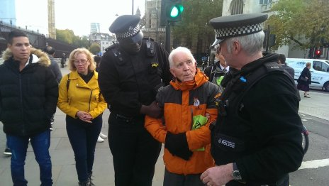 Phil Kingston is led away by police after blocking the road for several hours