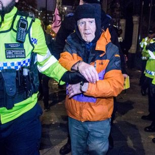 Phil Kingston, 82 , is led away from the Brazilian Embassy by police