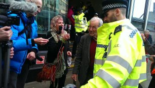 Reggie Norton, 85, is led away by police